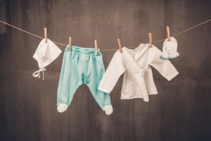 White baby goods hanging on the clothesline on grey background